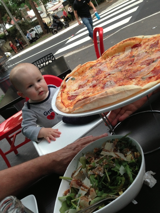 Lukas in awe of the heavenly feast before him (Genesis salad, $16, Assisi pizza, $22)